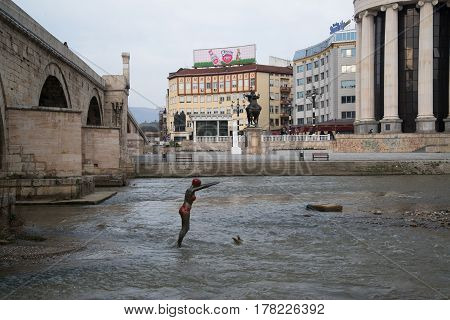 SKOPJE, MACEDONIA - March 20, 2017: Bronze statue of girl swimmer jumping in Vardar river at Skopje. Bronze statue of girl swimmer at Vardar river in Skopje, Macedonia.