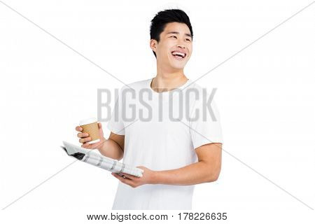 Young man looking away and smiling while reading newspaper on white background