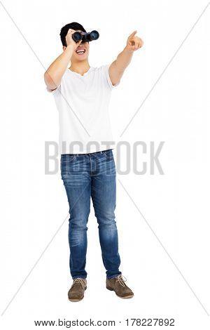 Young man looking through binocular on white background