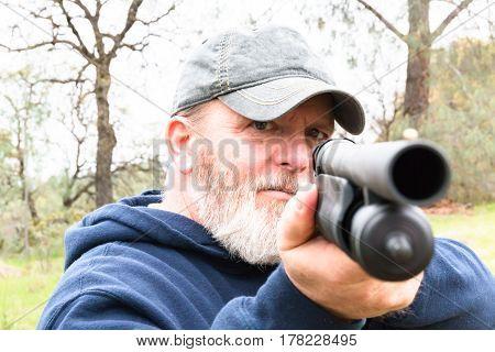 Close up of Man With White Beard Aiming Shotgun