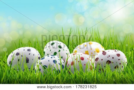 Easter egg background with coloured paint speckled easter eggs in long green grass with bright lights in blue sky