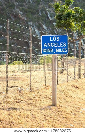 Abstract image of a sign post with Los Angeles 10158 miles away on a South African farm
