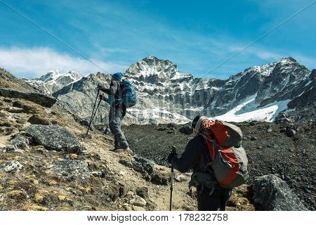 Mountain Climbers with Backpacks and walking Poles walking up on rocky Footpath toward high Altitude snowy Peak