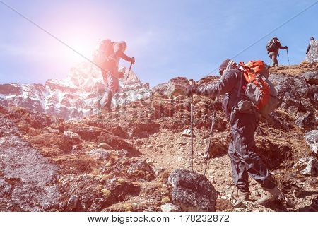 Silhouettes of Mountain Climbers with Backpacks and walking Poles walking up on rocky Footpath toward high Altitude snowy Peak Sun shining