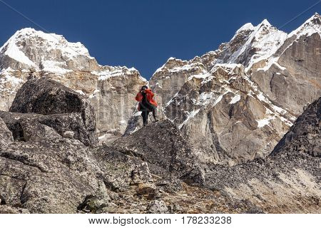 Mountain Climber in warm and red down Jacket taking Picture on photo camera staying on top of Rock
