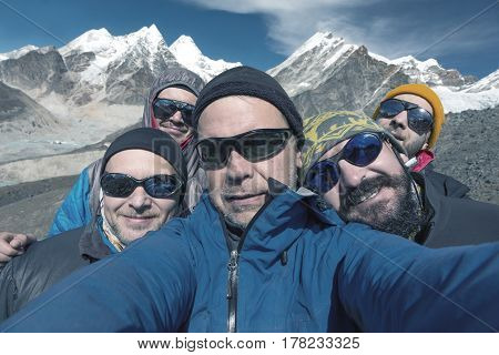 Self Portrait of Group of smiling and excited Mountain Climbers in windproof Jacket Sunglasses and Caps with high Peaks on Background