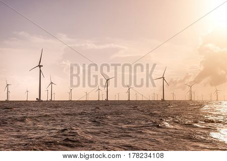 Wind turbines at sunset. Ecology wind against cloudy sky background with copy space