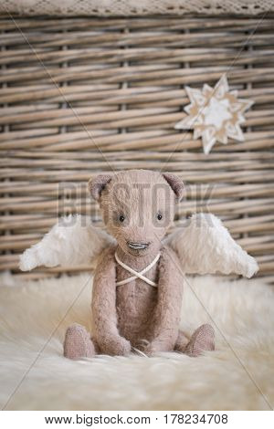 A teddy bear with angel wings sits on the background of a wicker basket