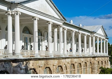 Antique vintage gallery with white columns on background of blue sky, sunlit