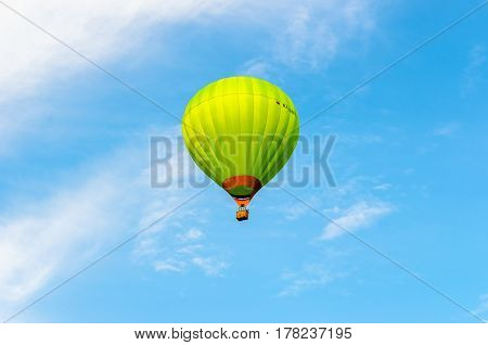 Green hot air balloon in flight against the blue sky and clouds.