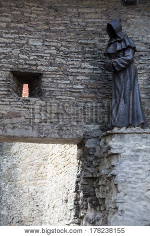 A statue of a monk on the wall of Tallinn