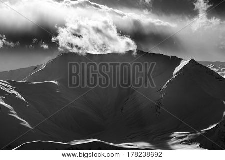 Black And White Mountains In Sunset With Sunlit Clouds