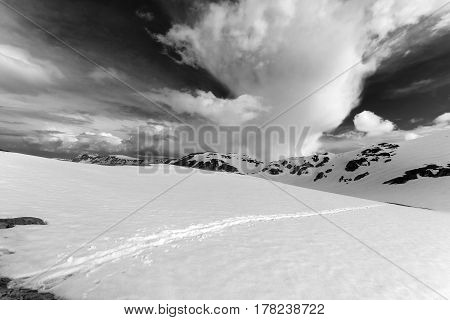 Black And White View On Snowy Mountains And Sky With Clouds