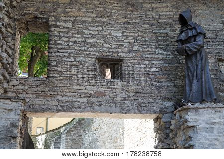 A statue of a monk on the wall of Tallinn, Estonia