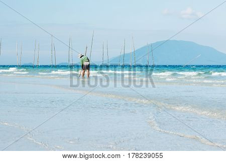 Man searching for small shells from the beach. A fisherman walking on the coast and using a special equipment to collect seashells that hide in the sand