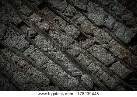 Old stone and wood wall texture background. Vintage dark toned