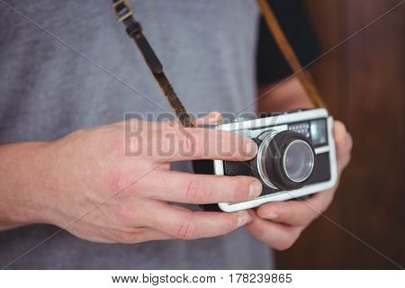 Handsome hipster holding retro camera with focus on hands