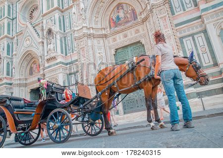 coach with a driver on the background of the Cathedral of Santa Maria Del Fiore in Florence Italy Europe