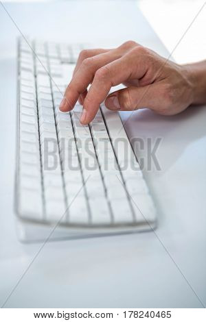 Close up view of a male hand typing on keyboard on white background