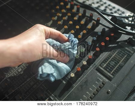 Male hand removing dust from old mixing console with wet cloth overhead composition