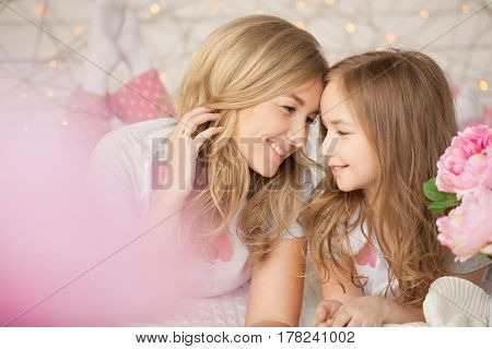 nyHappy family portrait. Mother and daughter laying in bed and smiling. Loft interior. Background with lights.