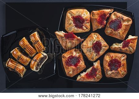 Poppy and jam cakes of a different form on small and big black square ceramic plates