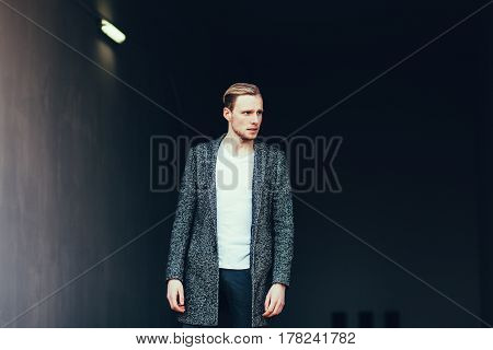 fashion man in coat outdoors. copy space