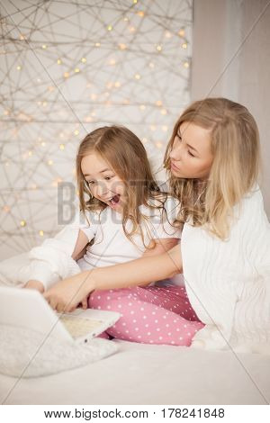 Mother and daughter sit on bed in pajamas and have fun, use laptop. Lifestyle. Happy family. Education, learn. Pastel colors