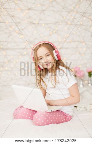 Music and technology. Portrait of young girl in pajamas with white laptop and wireless pink headphones on background with lights. Pastel colors. Indoor