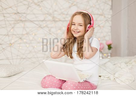 Music and technology. Portrait of young girl in pajamas with white laptop and wireless pink headphones on background with lights. Pastel colors