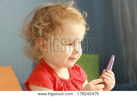 Pretty curly little girl in red t-shirt