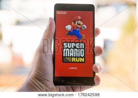 Nitra, Slovakia, march 26, 2017: A hand holding a smartphone with the the Super Mario Run game app. An illustrative editorial image.