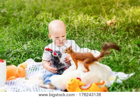 little child spring in the park amazedly looks on insolent squirrel.
