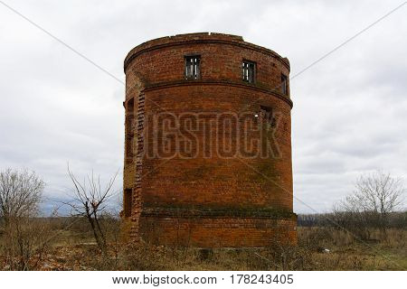 The old destroyed water tower standing alone in the field