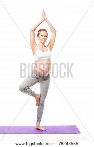 Full Body Studio Portrait Of Pregnant Blond Woman Doing Yoga On a Purple Exercise Mat. isolated on white studio background