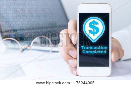 Business man is holding smartphone with transaction complete icon