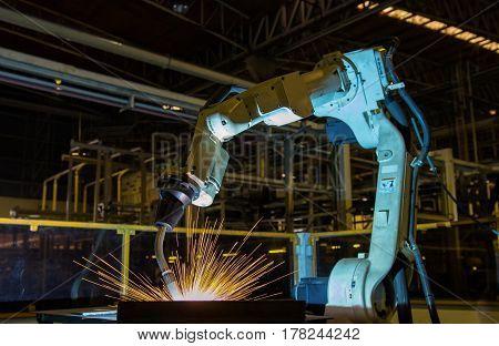 Robot is welding automotive part in factory