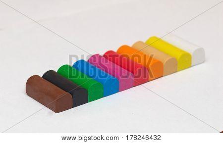Set of ten colorful plasticine spirals on a white background.