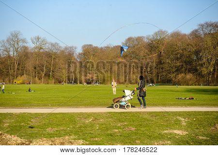 Munich,Germany-March 232017:A woman pushing a stroller watches a man flying a kite in the Englischer Garten