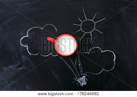 Frothy cappuccino in red mug on blackboard with a pattern of sun and clouds / journey with coffee