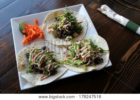 Large white plate with three tacos filled with rib-eye, drenched in  a sweet-tangy bbq sauce for dinner in restaurant.