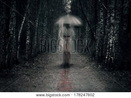 Scary woman ghost with knife stays in dark forest path