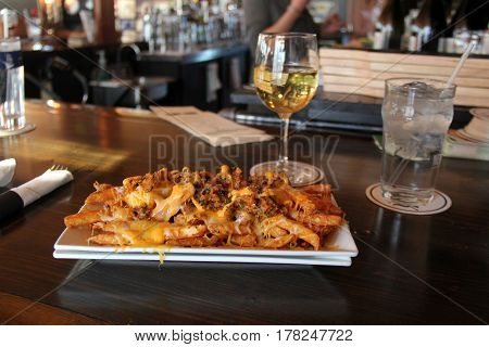 Large white plate with cheesy fries, glasses of wine to the side