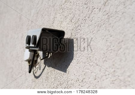 Closed circuit security and surveillance camera mounted on a rough cast plaster wall in sunshine with copy space alongside