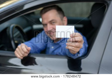Middle Aged Man Leaning From A Car Showing His Licence