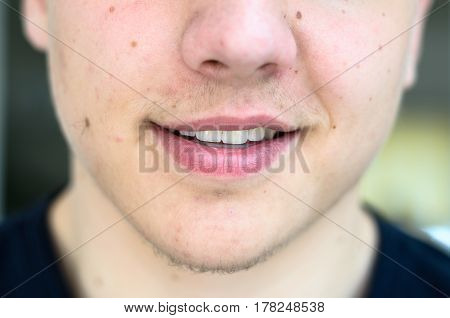 Close up view of the lower face of a young man with lips ajar and light stubble on his chin and upper lip