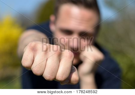 Determined Young Man Punching At The Camera