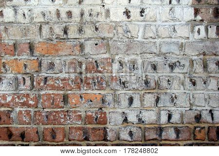 Old, weathered brick background, with peeling white paint and black hash marks