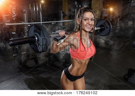 Attractive young woman working out with bar. Fitness girl sexy