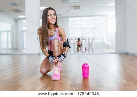 Sexy Sports Athletic Smile Girl Ties The Laces. White Positive Gym